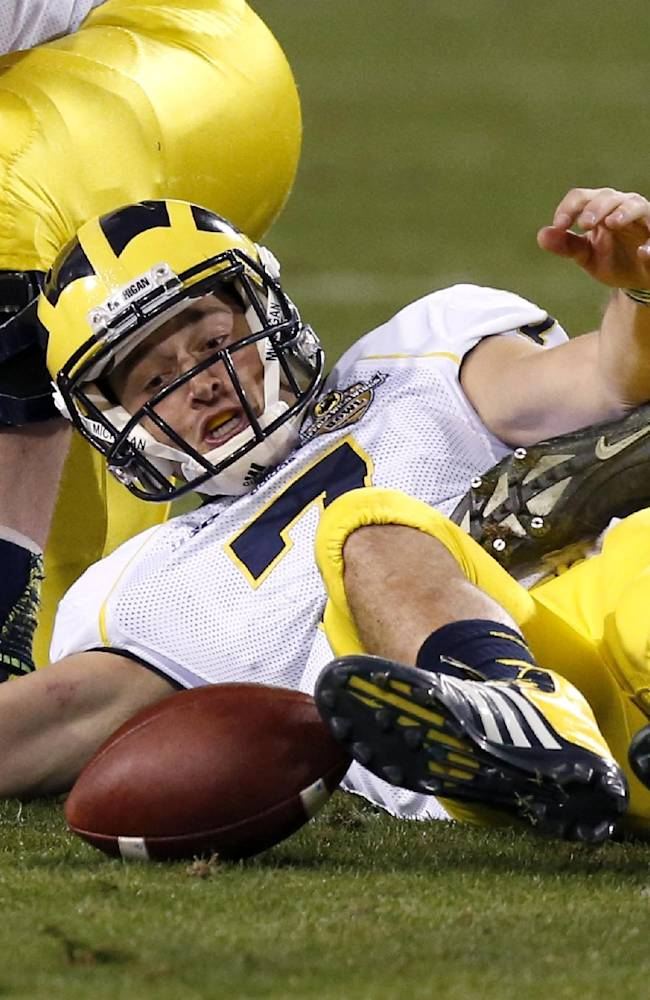 Michigan's Shane Morris fumbles the ball, which he later recovered, during the second half of the Buffalo Wild Wings Bowl NCAA college football game against Kansas State, Saturday, Dec. 28, 2013, in Tempe, Ariz. Kansas State defeated Michigan 31-14