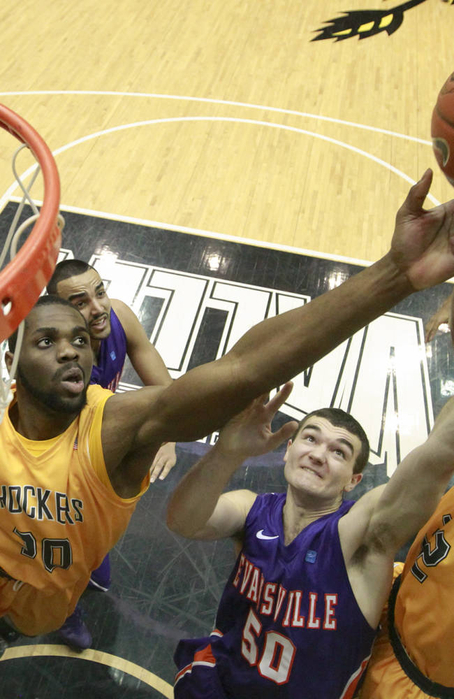 Wichita State's Tekele Cotton, right, and Kadeem Coleby, left, battle Evansville's Blake Simmons for a rebound during the second half of an NCAA college basketball game in Wichita, Kan., Saturday, Feb. 1, 2014