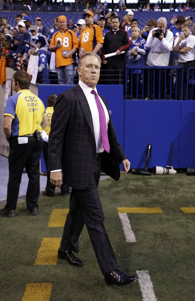 Former Denver Broncos quarterback, Broncos Executive Vice President of Football Operations John Elway walks on to the field before the NFL football game between the Indianapolis Colts and the Denver Broncos, Sunday, Oct. 20, 2013, in Indianapolis