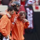 Oklahoma State quarterback Wes Lunt, center, is helped off the field after an injury in the first quarter of an NCAA college football game against Louisiana-Lafayette in Stillwater, Okla., Saturday, Sept. 15, 2012. (AP Photo/Sue Ogrocki)