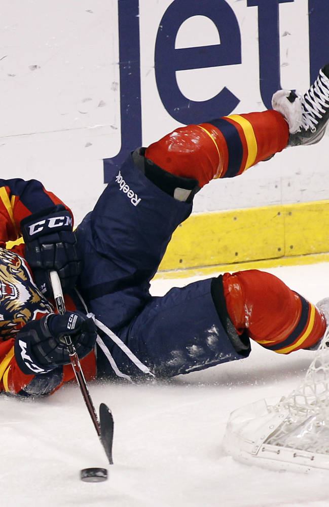 Florida Panthers center Vincent Trocheck (67) passes the puck as he falls to the ice during the first period of an NHL hockey game against the Dallas Stars in Sunrise, Fla., Sunday, April 6, 2014