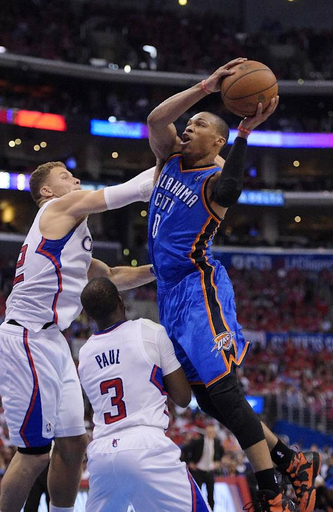 Oklahoma City Thunder guard Russell Westbrook, right, goes up for a shot as Los Angeles Clippers forward Blake Griffin, left, and guard Chris Paul, below, defend in the second half of Game 3 of the Western Conference semifinal NBA basketball playoff series, Friday, May 9, 2014, in Los Angeles. The Thunder won 118-112