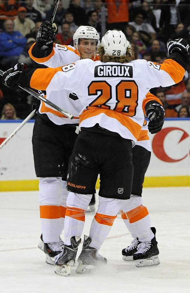 Philadelphia Flyers' Vincent Lecavalier (40) celebrates his hat trick goal with Claude Giroux (28) and Maxime Talbot in the third period of an NHL hockey game at the Nassau Coliseum on Saturday, Oct. 26, 2013, in Uniondale, N.Y. The Flyers won 5-2