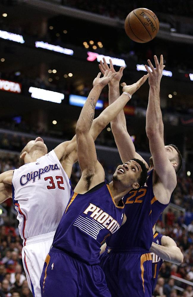 Los Angeles Clippers' Blake Griffin, left, fights for a rebound with Phoenix Suns' Gerald Green, center, and Miles Plumlee during the first half of an NBA basketball game on Monday, Dec. 30, 2013, in Los Angeles