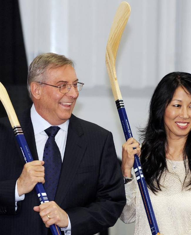 In this April 13, 2013, file photo, Buffalo Sabres' owner Terry Pegula and his wife, Kim Pegula, pose for cameras during groundbreaking ceremonies at  First Niagara Center before an NHL hockey game against the Philadelphia Flyers in Buffalo, N.Y. The Sabres owners said in a statement on Friday, June 20, 2014, that they have a strong desire to see the Bills stay in Buffalo, and aren't ruling out making a bid to buy the franchise. The statement was released a day after a person familiar with the sale process told The Associated Press the Pegulas were among prospective buyers who received a non-disclosure agreement and background on the Bills from a law firm representing late owner Ralph Wilson's estate