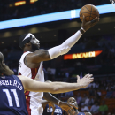 Miami Heat's LeBron James, center, slides through Charlotte Bobcats players Michael Kidd-Gilchrist (14), Josh McRoberts (11) and Al Jefferson (25) for two points during the first half of an NBA basketball game in Miami, Monday, March 3, 2014 The Associat