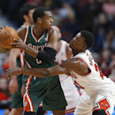 Chicago Bulls guard Jimmy Butler, right, reaches for the ball held by Milwaukee Bucks forward Khris Middleton during the first half of an NBA basketball game in Chicago, Friday, April 4, 2014 The Associated Press