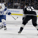 Toronto Maple Leafs right wing Phil Kessel, left, shoots under Los Angeles Kings defenseman Jeff Schultz during the first period of an NHL hockey game in Los Angeles, Monday, Jan. 12, 2015 The Associated Press