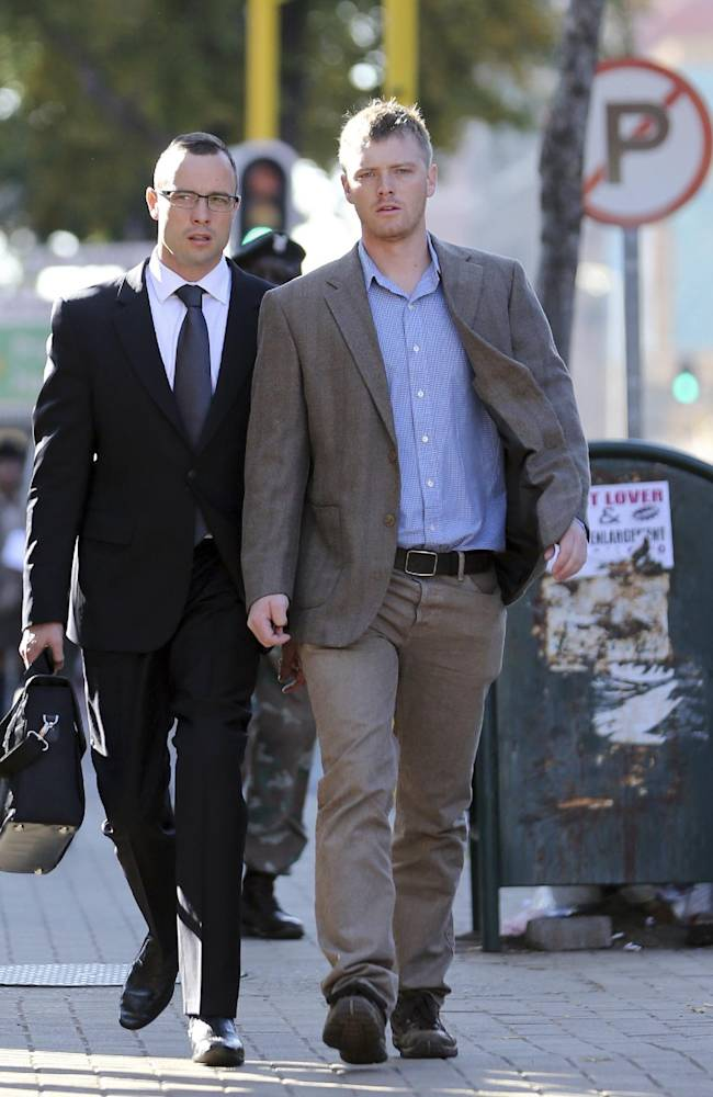 Oscar Pistorius, left, accompanied by an unidentified relative, walks towards the high court in Pretoria, South Africa, Wednesday, May 14, 2014. The chief prosecutor in the murder trial of Pistorius on Tuesday asked that the double-amputee runner be placed under psychiatric evaluation after an expert witness testified that he had an anxiety disorder. Pistorius is charged with murder for the shooting death of his girlfriend, Reeva Steenkamp, on Valentines Day in 2013. (AP Photo/Themba Hadebe)