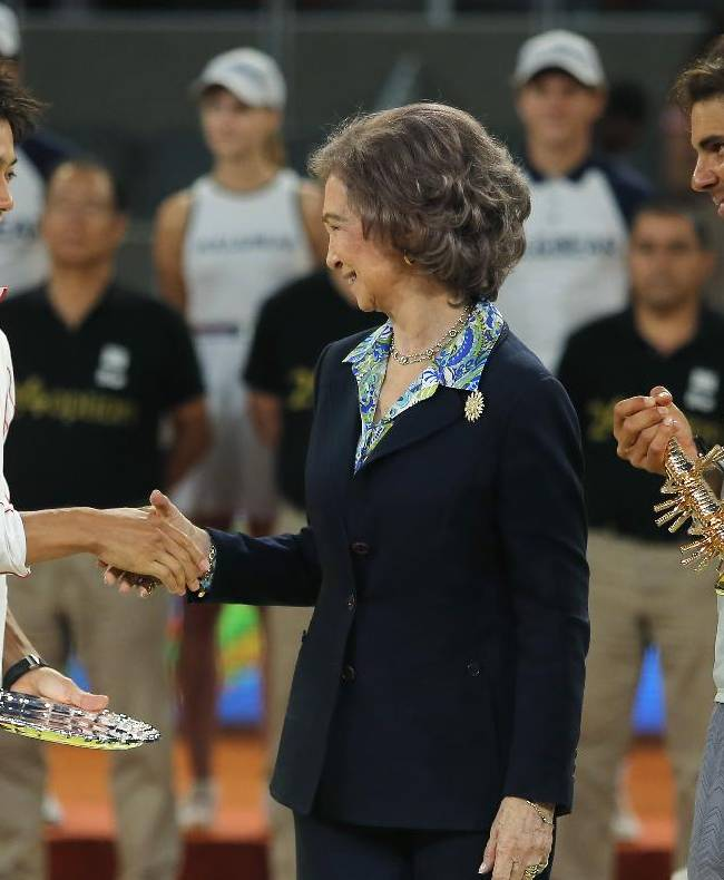 Kei Nishikori from Japan, left, shakes hands with Queen Sofia of Spain, center, as Rafael Nadal from Spain watches following their Madrid Open tennis tournament final match in Madrid, Spain, Sunday, May 11, 2014. Nadal won his fourth Madrid Open on Sunday after Nishikori was forced to withdraw with a hip injury when trailing 2-6, 6-4, 3-0 in the final