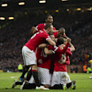 Manchester United's Robin van Persie, lower centre left, celebrates with teammates after scoring during the English Premier League soccer match between Manchester United and Liverpool at Old Trafford Stadium, Manchester, England, Sunday Dec. 14, 2014