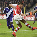 Arsenal's Alexis Sanchez, center, passes the ball to teammate Lukas Podolski who scored 2-1, passing Anderlecht's Olivier Deschacht, right, during the Group D Champions League match between Anderlecht and Arsenal at Constant Vanden Stock Stadium in Brusse