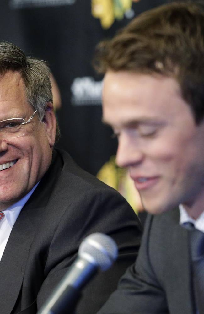 Rocky Wirtz, left, President of Wirtz Corporation and Chairman of the Chicago Blackhawks smiles as he listens to Jonathan Toews during a news conference at the United Center in Chicago, Wednesday, July 16, 2014. The Blackhawks recently agreed to eight-year contract extensions with Toews and Kane