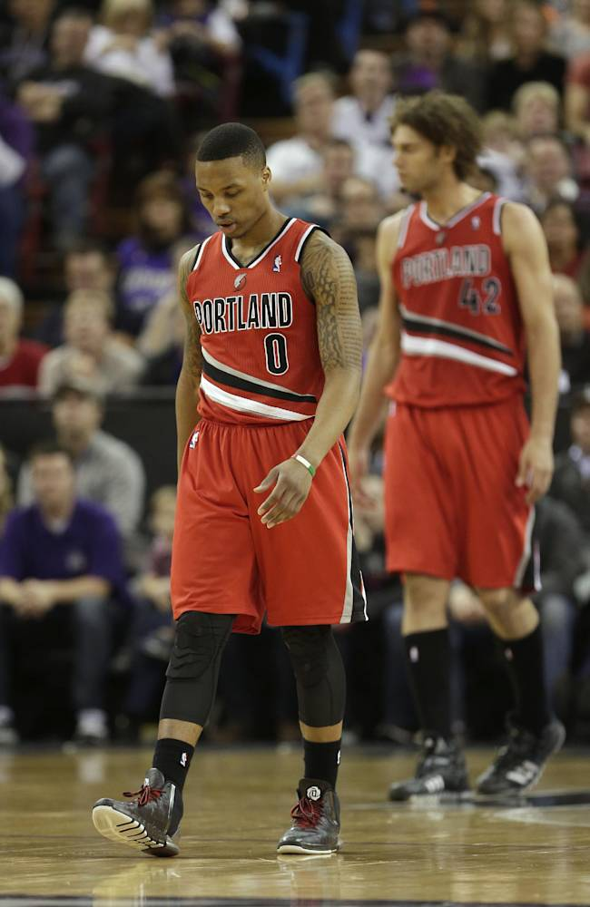 Portland Trail Blazers guard Damian Lillard, left, walks down court late in the fourth quarter of the Trail Blazers 123-119 loss to the Sacramento Kings in a NBA basketball game in Sacramento, Calif., Tuesday, Jan. 7, 2014