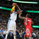 Denver Nuggets guard Randy Foye, left, launches a three-point basket over Houston Rockets guard Isaiah Canaan in the third quarter of the Nuggets' 123-116 victory in an NBA basketball game in Denver on Wednesday, April 9, 2014 The Associated Press