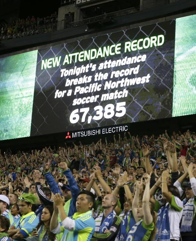 In this Aug. 25, 2013 file photo, fans cheer as a record-setting attendance of more than 67,000 is announced during a MLS soccer match between the Seattle Sounders and the Portland Timbers, in Seattle. Major League Soccer is growing, with more lucrative TV and sponsorship deals and greater attendance. But it hasn't yet translated into a television ratings breakthrough, and the league hopes the World Cup provides a long-lasting boost