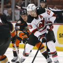 Anaheim Ducks' Ryan Getzlaf (15) and New Jersey Devils Travis Zajac (19) vie for the puck during the first period of an NHL hockey game, Friday, Jan. 16, 2015, in Anaheim, Calif The Associated Press