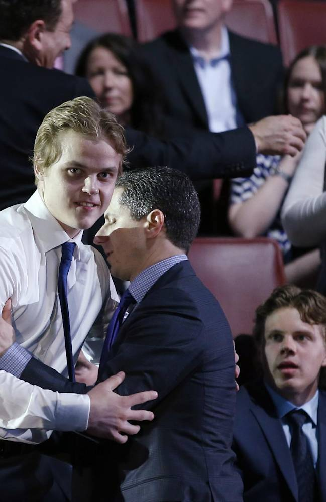 Julius Honka is congratulated before he walks to the stage after being chosen 14th overall by the Dallas Stars during the first round of the NHL hockey draft, Friday, June 27, 2014, in Philadelphia