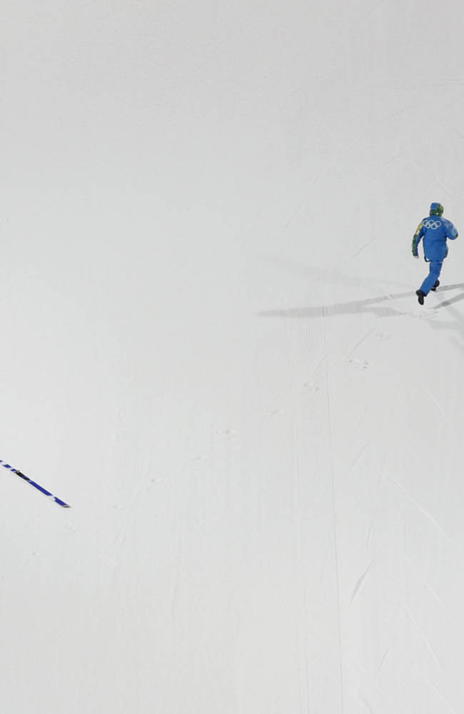 A volunteer retrieves the skis after Norway's Anders  Jacobsen fell after an attempt in the men's normal hill ski jumping at the 2014 Winter Olympics, Thursday, Feb. 6, 2014, in Krasnaya Polyana, Russia