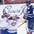 Montreal Canadiens' Tomas Plekanec, center, celebrates his game-winning goal with teammate Andrei Markov, left, in front of Toronto Maple Leafs' Roman Polak during third-period NHL hockey game action in Toronto, Wednesday, Oct. 8, 2014 The Associated Pres