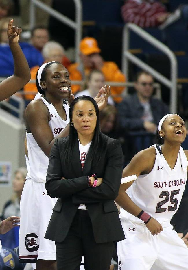 South Carolina  players from left; forward Aleighsa Welch (24), center Alaina Coates (41) and Tiffany Mitchell (25) celebrate behind head coach Dawn Staley in the second half of a quarterfinal women's Southeastern Conference tournament NCAA college basketball game against Georgia Friday, March 7, 2014, in Duluth, Ga.  South Carolina  won 67-48