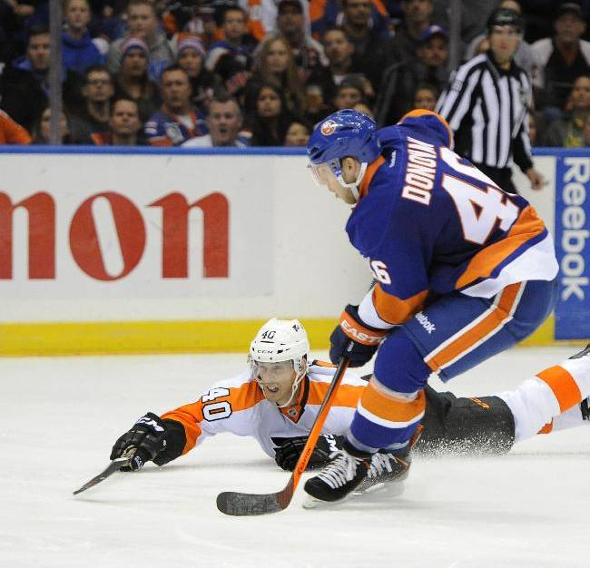 Philadelphia Flyers' Vincent Lecavalier (40) falls to the ice to push shoot the puck past New York Islanders' Matt Donovan (46) in the third period of an NHL hockey game at the Nassau Coliseum on Saturday, Oct. 26, 2013, in Uniondale, N.Y. Lecavalier scored three goals during the Flyers 5-2 win