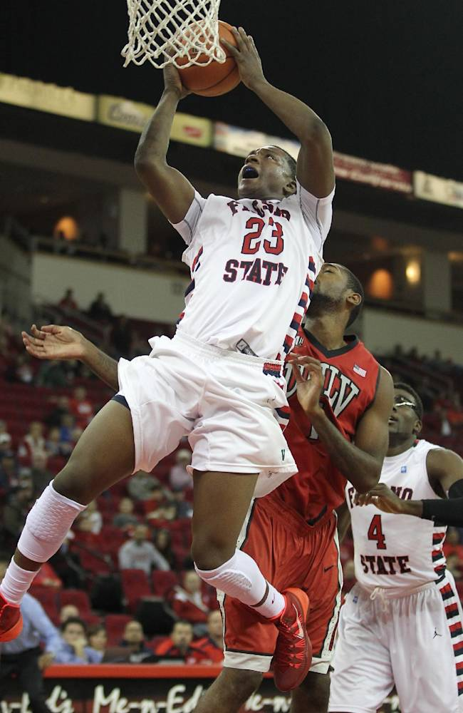 Fresno State's Marvelle Harris is fouled on his way to a lay-up by UNLV's Roscoe Smith in the second half of an NCAA college basketball game in Fresno, Calif., Wednesday, Jan. 1, 2014