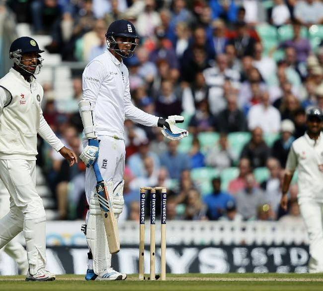 England's Stuart Broad, right, holds out his left hand to show the umpire that the ball hit his hand that was not on the bat, as he argues that he not be given out during the third day of the fifth test cricket match against India at Oval cricket ground in London, Sunday, Aug. 17, 2014