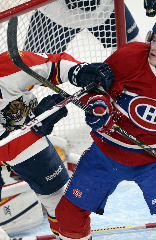 Montreal Canadiens right wing Brendan Gallagher (11) and Florida Panthers defenseman Mike Weaver (43) battle in front of the net during first-period NHL hockey action on Sunday, Dec. 15, 2013, in Montreal