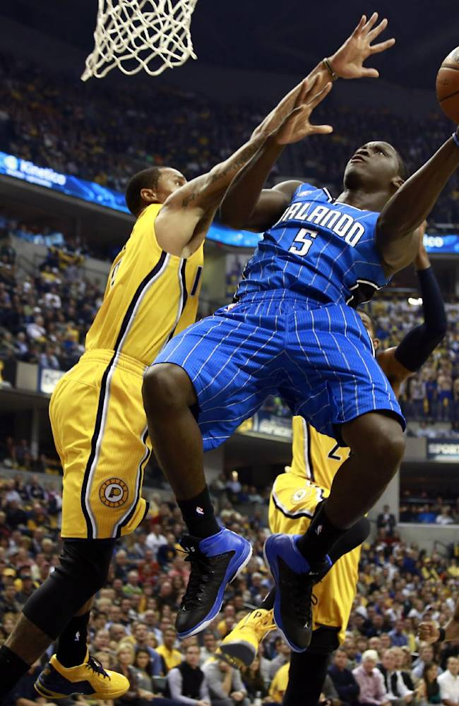 Orlando Magic guard Victor Oladipo (5) puts up a shot while defended by Indiana Pacers guard George Hill in the first half of an NBA basketball game in Indianapolis, Tuesday, Oct. 29, 2013