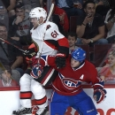 Montreal Canadiens' Brandon Prust, right, checks Ottawa Senators' Andre Benoit into the boards during third-period NHL hockey