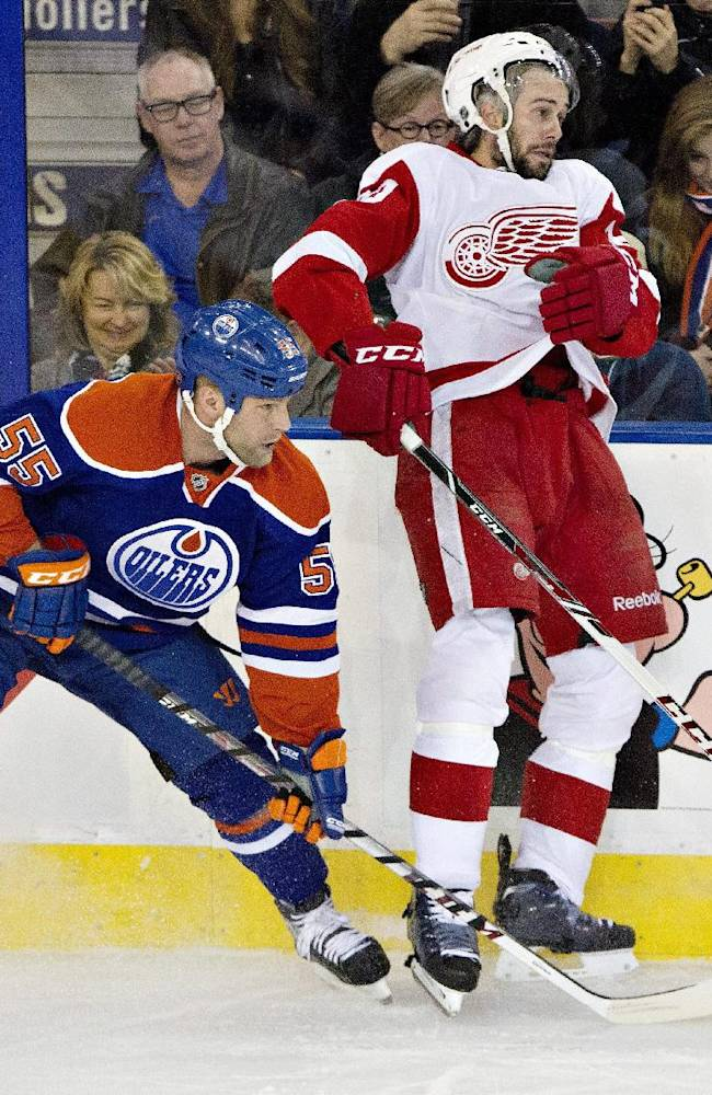 Detroit Red Wings' Drew Miller (20) is checked by Edmonton Oilers' Ben Eager (55) during the second period of an NHL hockey game on Saturday, Nov. 2, 2013, in Edmonton, Alberta