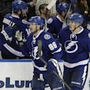 Tampa Bay Lightning right wing Nikita Kucherov (86), of Russia, and defenseman Matt Carle celebrate with the bench after Kucherov scored against the New York Rangers during the third period of an NHL hockey game Wednesday, Nov. 26, 2014, in Tampa, Fla. The Lightning defeated the Rangers 4-3. (AP Photo/Chris O'Meara)
