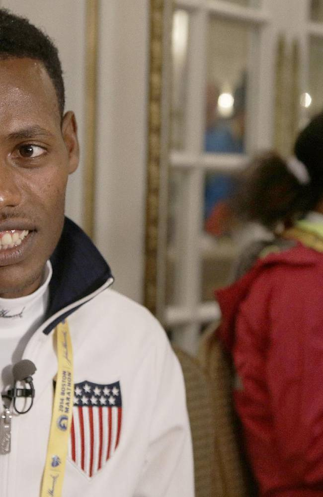 Last year's winner of the Boston Marathon, Lelisa Desisa, of Ethiopia, wears a USA warm-up jacket as he talks with a reporter during a media availability of Boston Marathon elite runners at the Copley Plaza Hotel in Boston Friday April 18, 2014. Runner Buzunesh Deba of Ethiopia sits alone at right. The 118th running of the Boston Marathon is Monday April 21, 2014