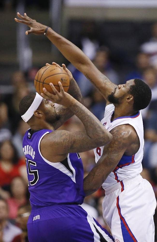 Sacramento Kings center DeMarcus Cousins shoots the ball as Los Angeles Clippers center DeAndre Jordan defends him during the first half of an NBA basketball game in Los Angeles, Sunday, April 12, 2014