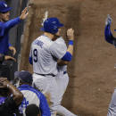 Los Angeles Dodgers catcher Yasmani Grandal, left, congratulates Alex Guerrero after his grand slam off Colorado Rockies relief pitcher Rafael Betancourt in the ninth inning of the second game of a baseball doubleheader Tuesday, June 2, 2015, in Denver. (AP Photo/David Zalubowski)