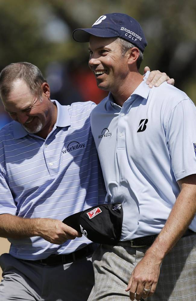 Matt Kuchar, right, walks off the 18th green with playing partner Jerry Kelly, left, after they both birdied the hole during the third round of the Texas Open golf tournament, Saturday, March 29, 2014, in San Antonio