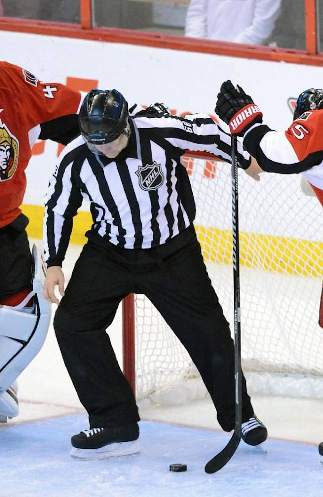 A linesman fishes the puck from the net as Ottawa Senators' Craig Anderson, left, and Erik Karlsson stands during the third period of an NHL hockey game in Ottawa, Ontario, Sunday, Nov. 17, 2013