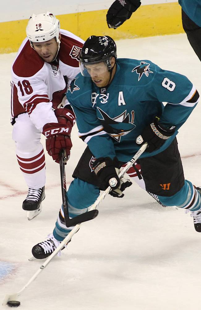 Sharks' Joe Pavelski (8) clears the puck from the crease as the Coyotes' Dave Moss chases during the first period of an NHL preseason hockey game in San Jose, Calif., Saturday, Sept. 21, 2013