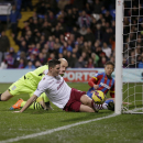 Aston Villa's Ciaran Clark, center, clears the ball off the line watched by goalkeeper Brad Guzan, left, and Crystal Palace's Dwight Gayle during the English Premier League soccer match between Crystal Palace and Aston Villa at Selhurst Park stadium in Lo