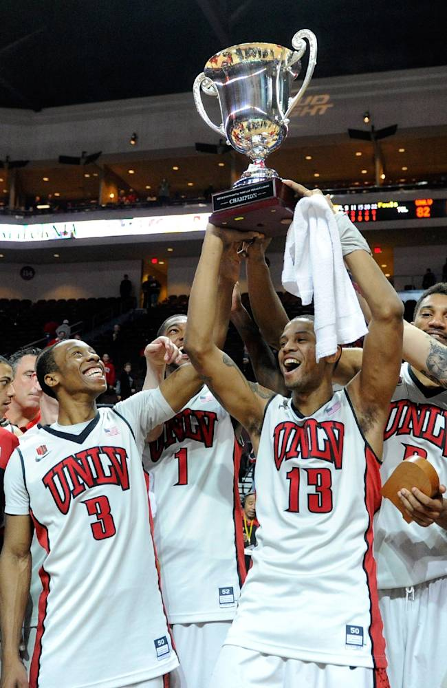 UNLV's Kevin Olekaibe (3), Roscoe Smith (1), Bryce Dejean-Jones (13) and Khem Birch celebrate with the tournament championship trophy after defeating Mississippi State at an NCAA college basketball game on Monday, Dec. 23, 2013, in Las Vegas. UNLV won 82-66