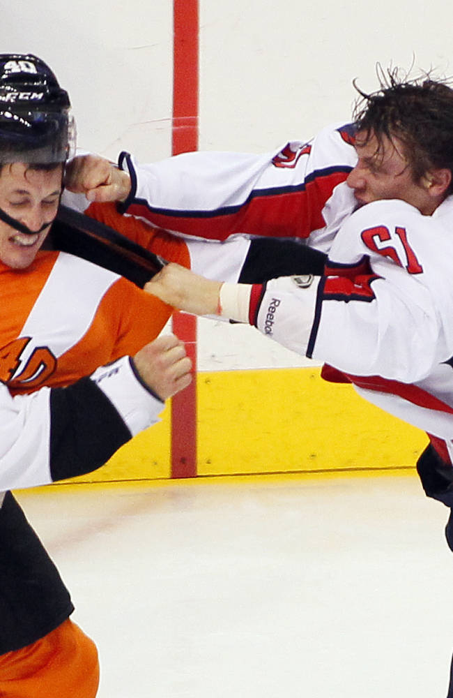Philadelphia Flyers' Vincent Lecavalier, left, takes a punch to his head from  Washington Capitals' Steve Olesky knocking his helmet off during a melee in the third period of an NHL hockey game Friday, Nov. 1, 2013, in Philadelphia. The Capital won 7-0