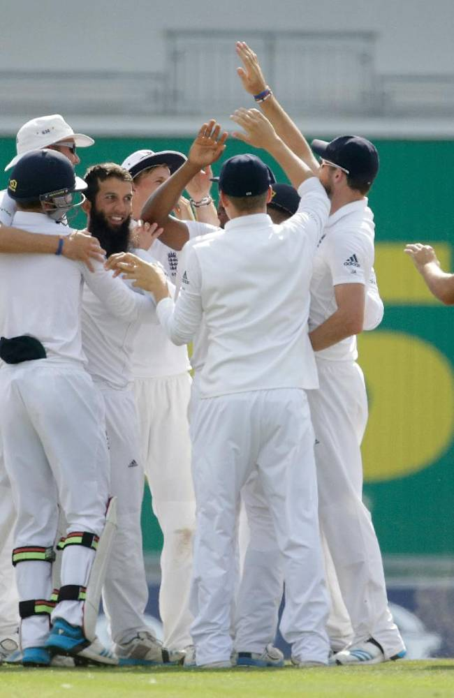 England's Moeen Ali, third left, celebrates with his teammates after taking the wicket of India's Cheteshwar Pujara during the fourth day of the third cricket Test match of the series between England and India at The Ageas Bowl in Southampton, England, Wednesday, July 30, 2014