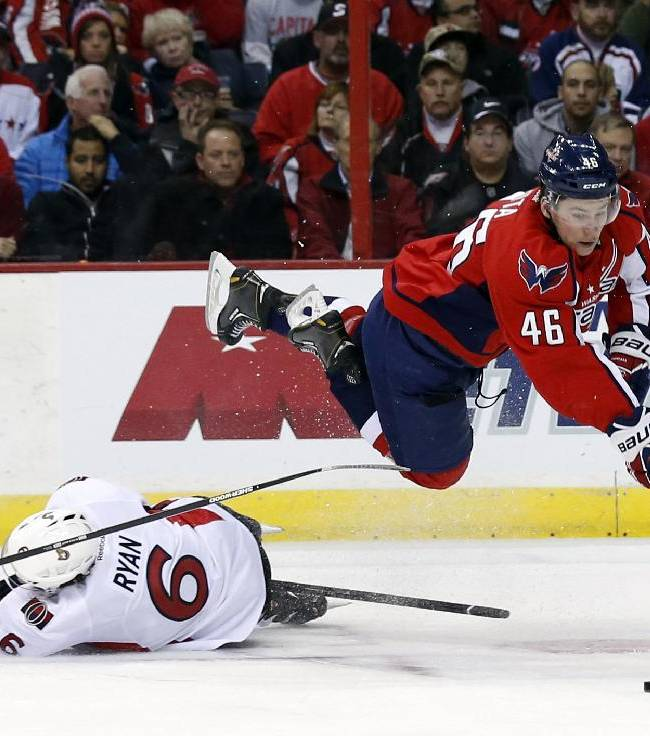 Washington Capitals center Michael Latta (46) dives over Ottawa Senators right wing Bobby Ryan (6) for the puck, to pass to right wing Eric Fehr, who scored on the play giving Latta an assist, during the first period of an NHL hockey game, Wednesday, Nov. 27, 2013, in Washington