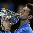 Novak Djokovic of Serbia holds the trophy after defeating Andy Murray of Britain in the men's singles final at the Australian Open tennis championship in Melbourne, Australia, Sunday, Feb. 1, 2015. (AP Photo/Vincent Thian)