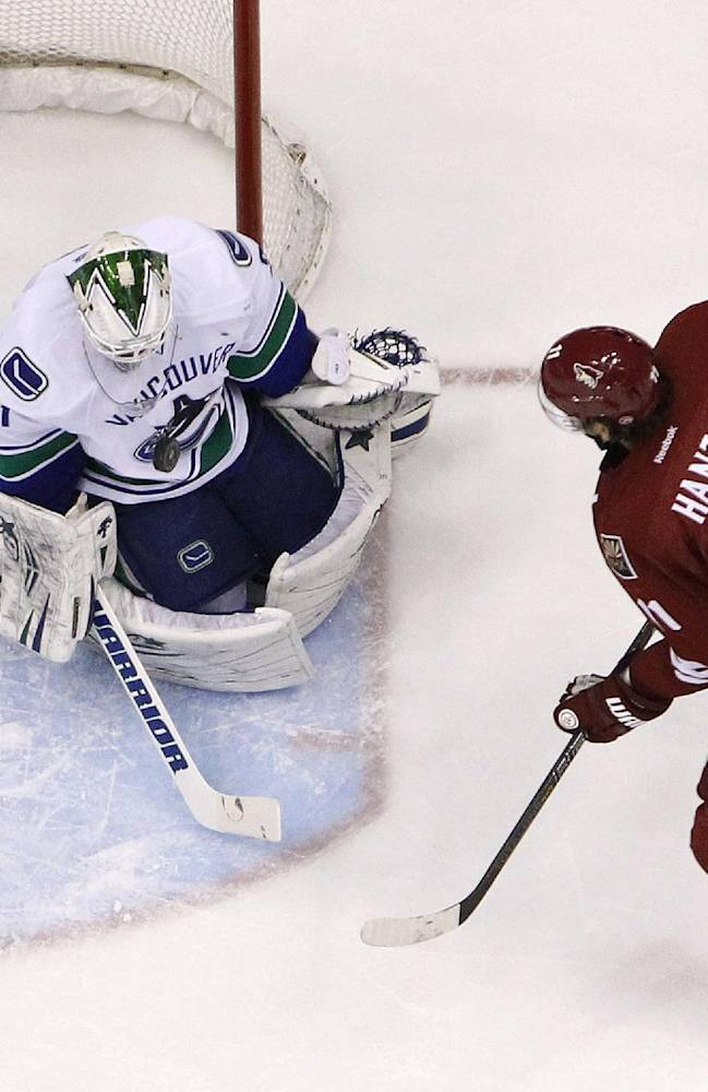 Vancouver Canucks' Eddie Lack (31) makes a save on a shot by Phoenix Coyotes' Martin Hanzal (11), of the Czech Republic, during the first period of an NHL hockey game Thursday, Jan. 16, 2014, in Glendale, Ariz.  The Coyotes defeated the Canucks 1-0