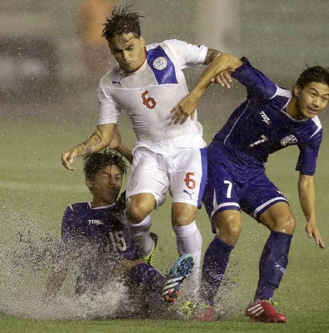 The Philippines' Jason De Jong (6) is challenged by Taiwan's Weng Wei-pin (15) and Chiu J-huan (7) during the Peace Cup 2014 soccer friendly match  Wednesday, Sept.3, 2014 at the rain-soaked Rizal Memorial Football Stadium in Manila, Philippines