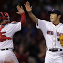 Boston Red Sox relief pitcher Koji Uehara, right, high-fives catcher Christian Vazquez after the Red Sox defeated the Tampa Bay Rays 11-1 during a baseball game at Fenway Park in Boston, Thursday, Sept. 25, 2014. (AP Photo/Charles Krupa)