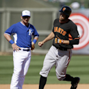 San Francisco Giants' Hunter Pence, rounds third as Kansas City Royals' Danny Valencia, left, watches following a solo home run by Pence off Royals relief pitcher Wade Davis in the sixth inning of a spring training baseball game, Friday, March 7, 2014, in