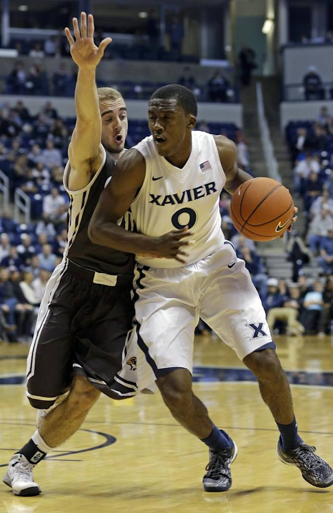 Xavier guard Semaj Christon (0) drives against Quincy guard Grant Meyer in the first half of an NCAA exhibition college basketball game, Saturday, Nov. 2, 2013, in Cincinnati